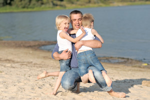 portrait of a father and two sons on the beach